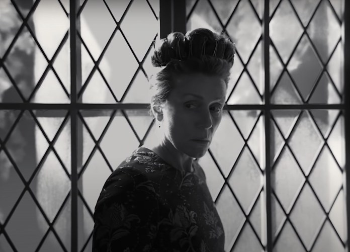Frances McDormand as Lady Macbeth in the trailer for 'The Tragedy of Macbeth'.  In the black-and-white photo, McDormand is wearing a dark dress with floral embellishments, high-rise hair and a crown around it.  She stands in front of a large window lined with diamond lattice and looks worried.  McDormand co-stars in the film with Denzel Washington, who plays Lord Macbeth.