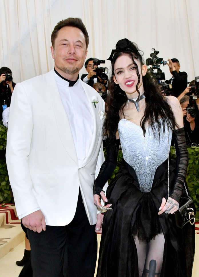 Elon Musk and Grimes smile for the camera together at the 2018 Met Gala.
