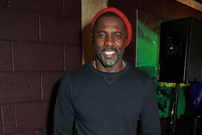 Idris Elba in a red hat at a premiere