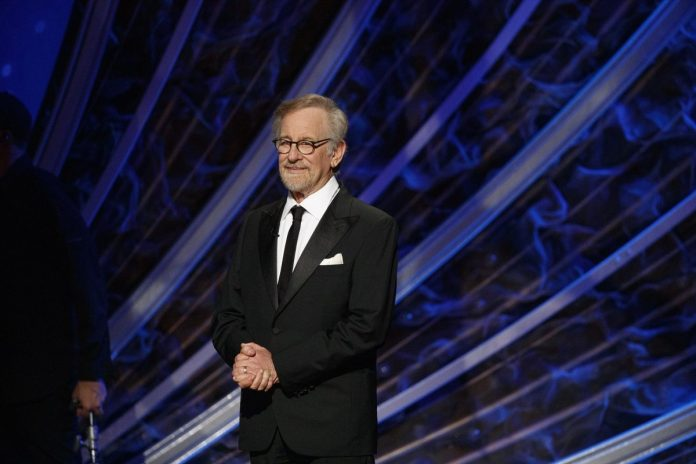 Steven Spielberg stood on stage with folded hands in front of him.