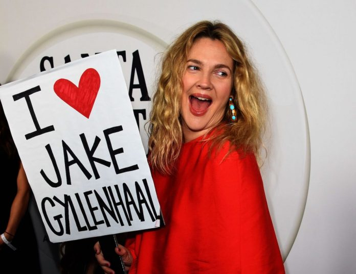 Drew Barrymore wears red and has a sign saying I love Jake Gyllenhaal in the Season 2 premiere of 'Santa Clarita Diet'.