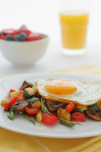 This quick Summer Vegetable Hash has all the goodness of zucchini, tomatoes, peppers and more making a delicious bed for a nice and runny fried egg.