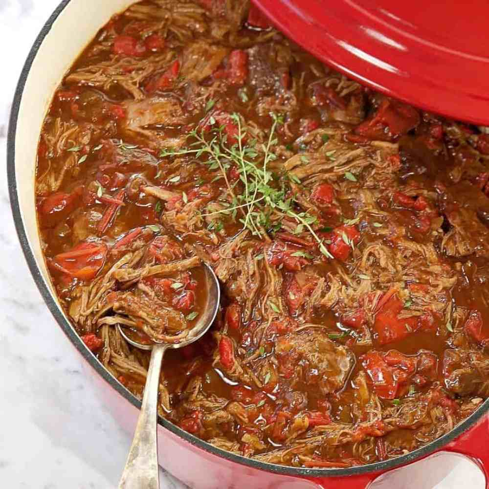 lamb with sauce in a red and white pot