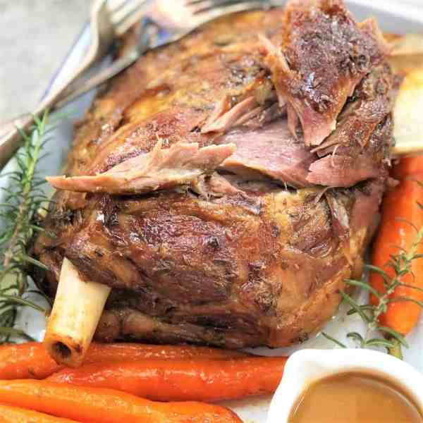 slow cooked pulled lamb shoulder in a white baking dish with carrots