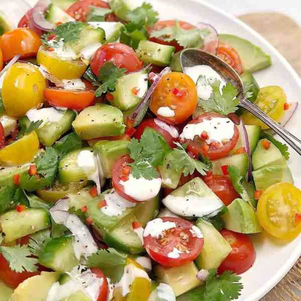 green avocado and red cherry tomatoes with a white dressing on a white plate