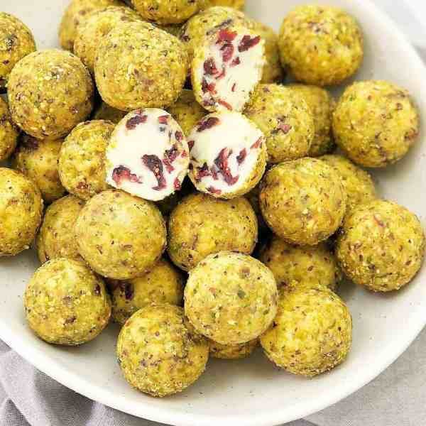 balls of white chocolate with red pieces coated in green pistachios sitting in a white bowl
