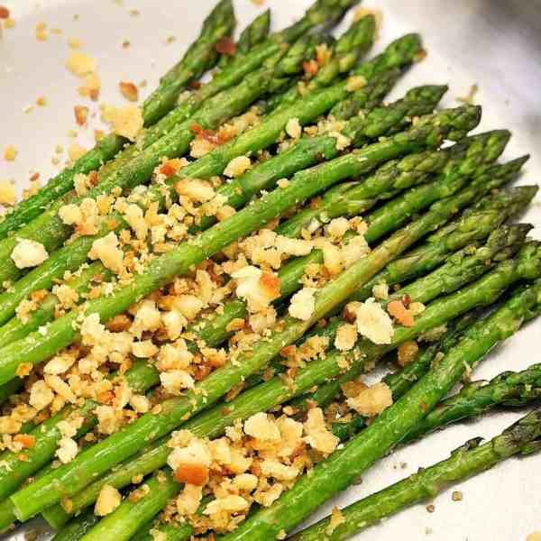 pile of green asparagus in a silver pan with crumbs on top