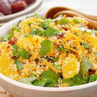 couscous, green coriander, slices of orange in a white bowl