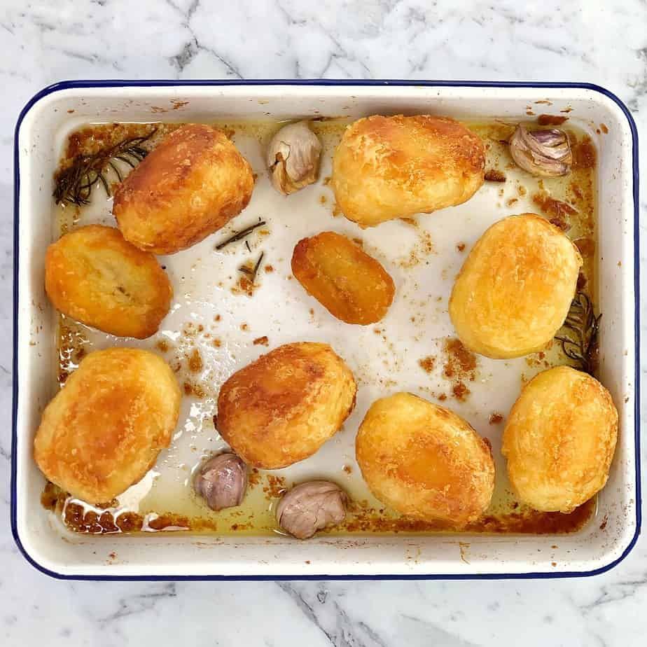 golden roast potatoes in a white baking dish