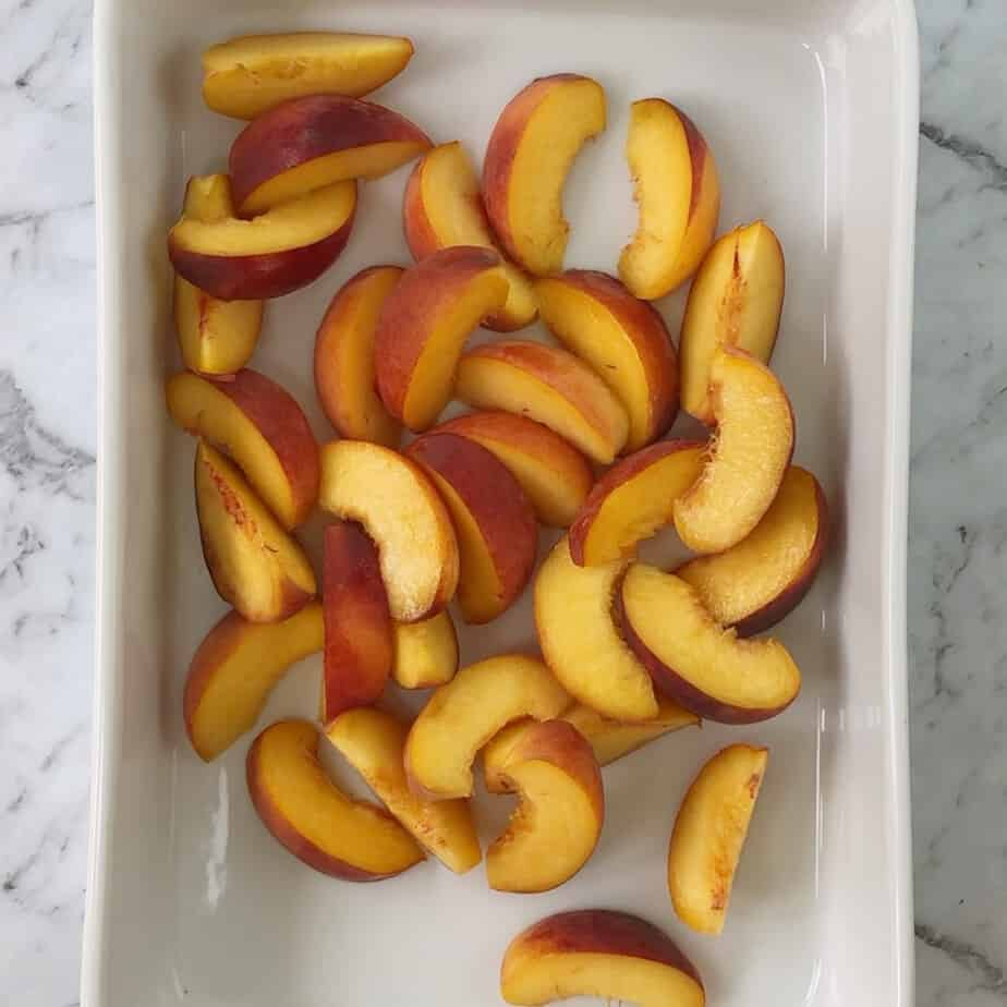 sliced peaches in a white baking dish