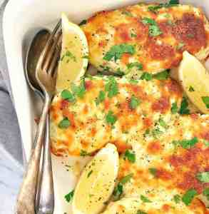 baked chicken breasts covered in cheese and pesto in a white dish