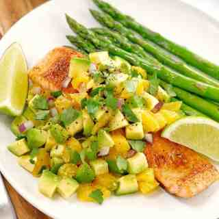 salmon fillet with chopped avocado and orange on a white plate