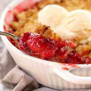 red strawberry mixture with brown crumble on top in a white dish with scoops of ice cream on top