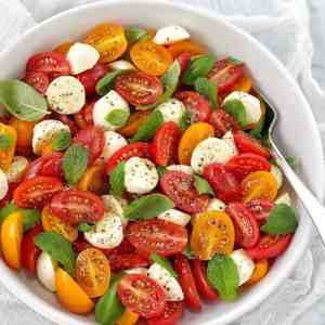 tomatoes bocconcini basil and mint in a white bowl