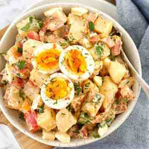 potato salad in a white bowl with sliced egg on top