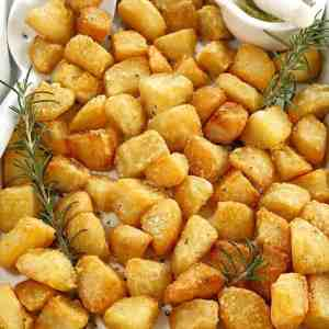 cubes of crisp potatoes in a white baking tray