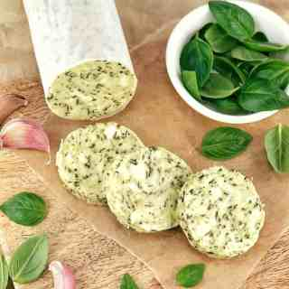 slices of compound butter and basil leaves on a bread board