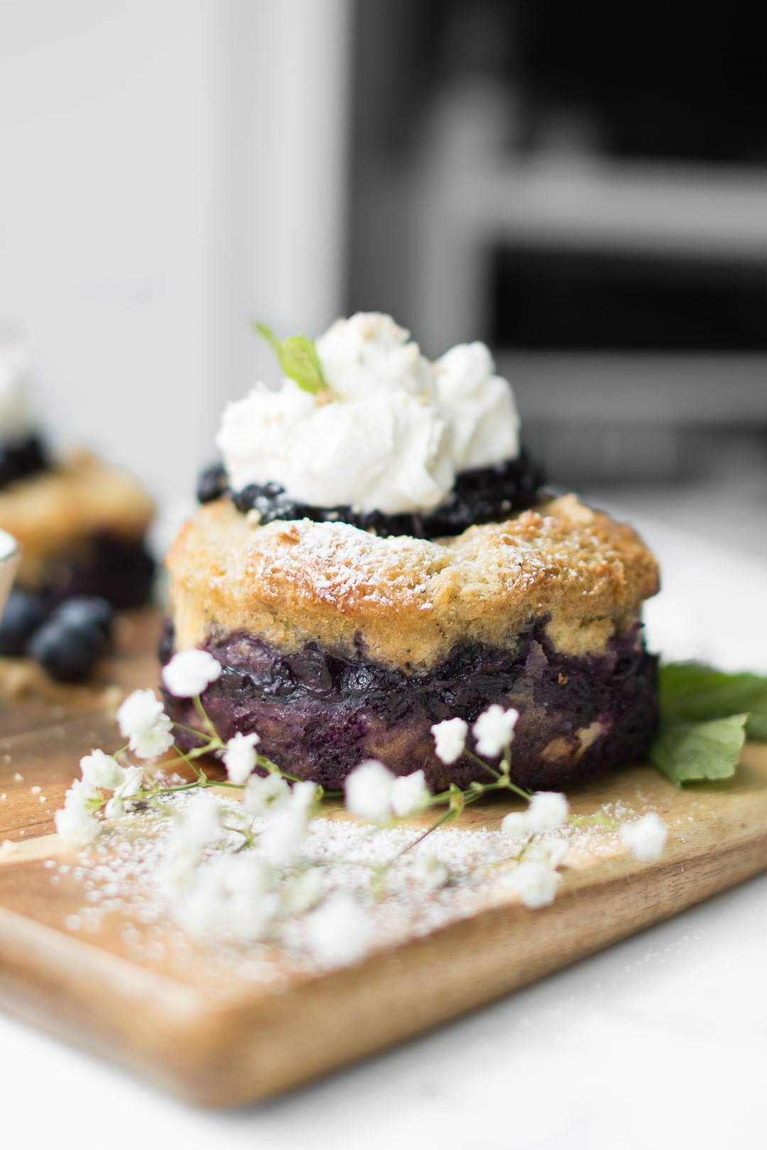 Blueberry French Toast Cake on a wooden board with baby's breath