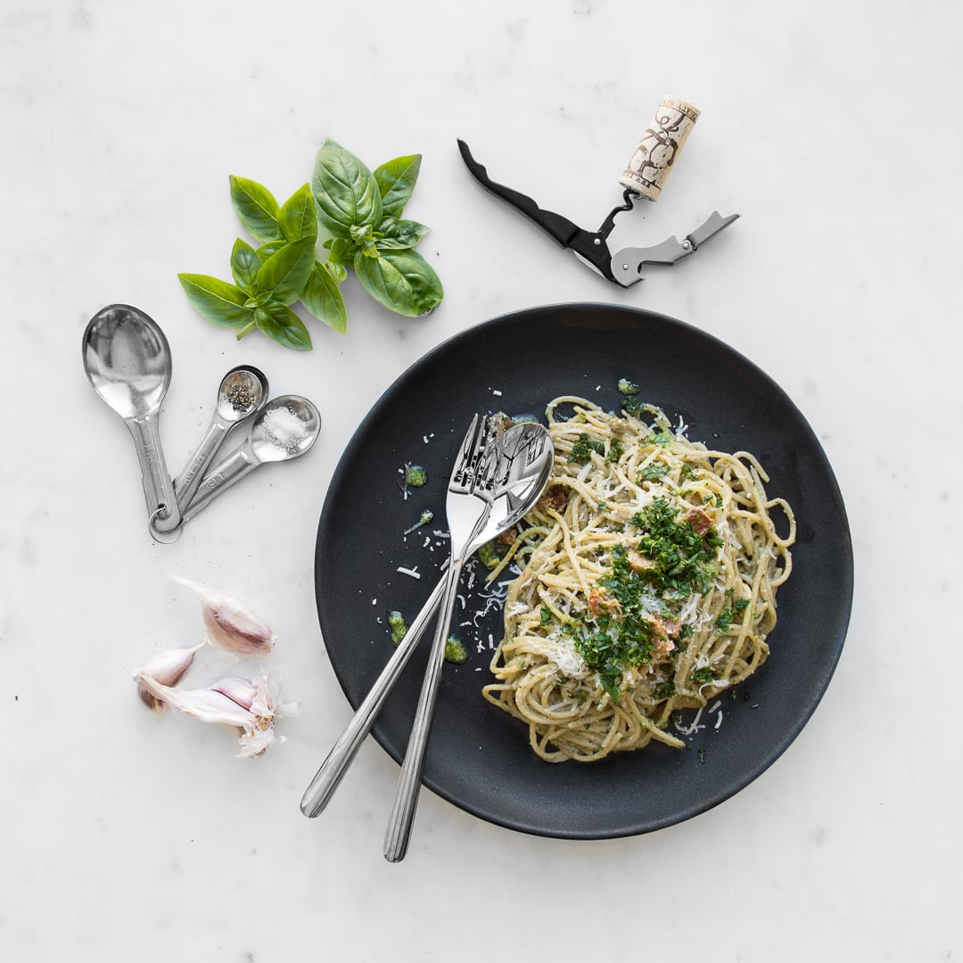 Overhead image of plated Pesto Carbonara on a black plate with a fork and spoon, laying on marble with basil, garlic cloves, and a corkscrew with a cork