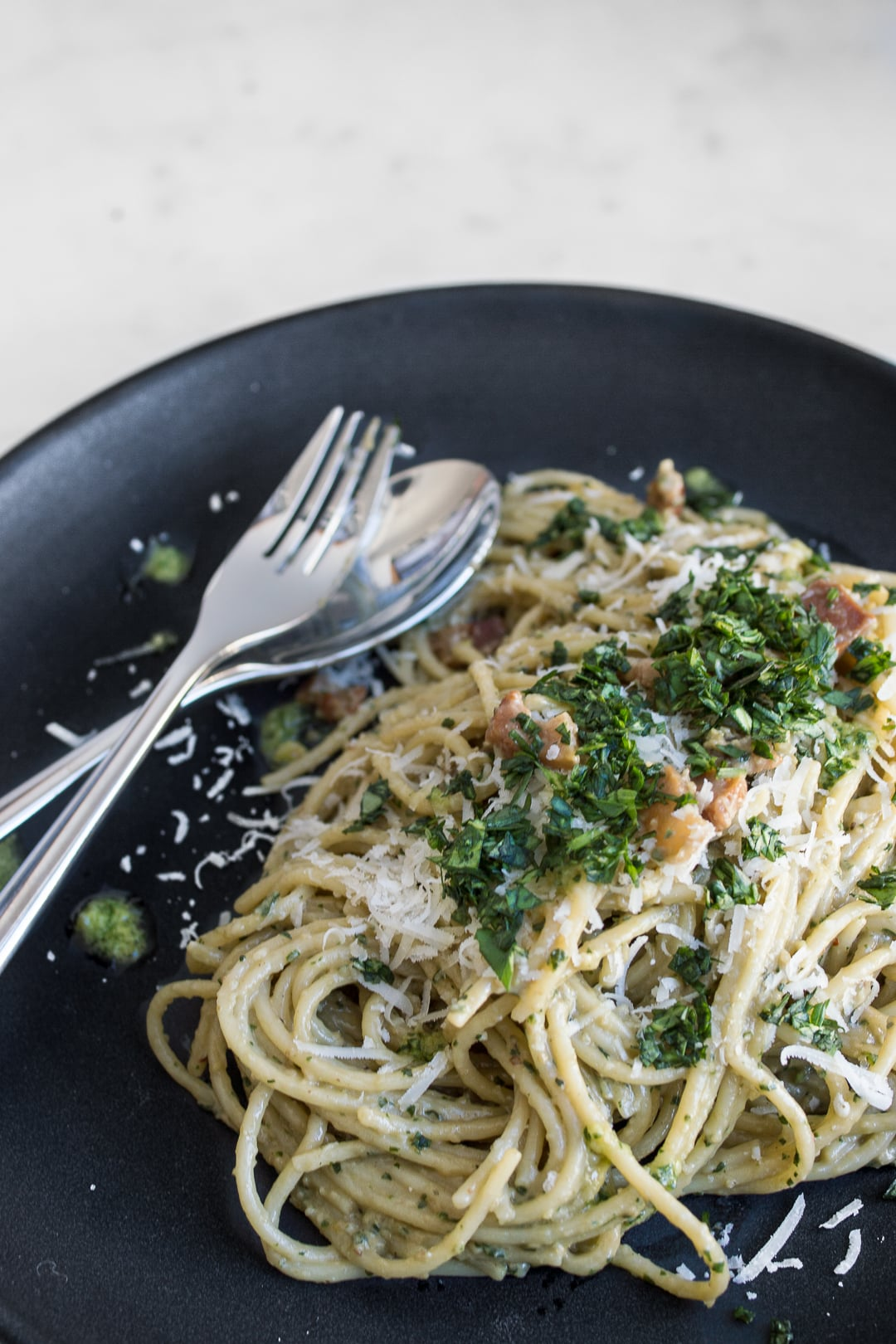 Close-up of Pesto Carbonara, topped with chopped basil and parmesan cheese, on a black plate with fork and spoon.