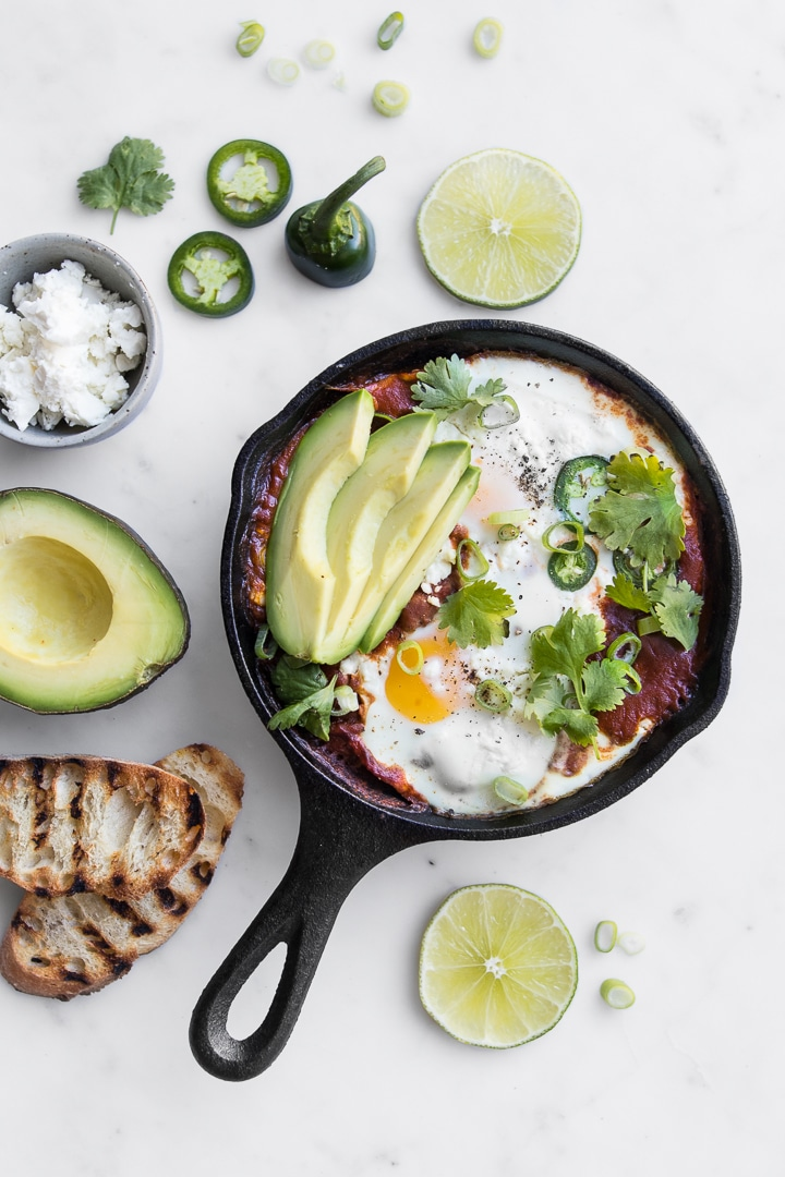 Small Cast Iron Skillet with Shakshouka topped with Sliced Avocado