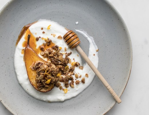 Roasted Pear with granola and yogurt on a grey plate with a honey stick