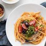 Spaghetti Puttanesca on a white plate with a napkin