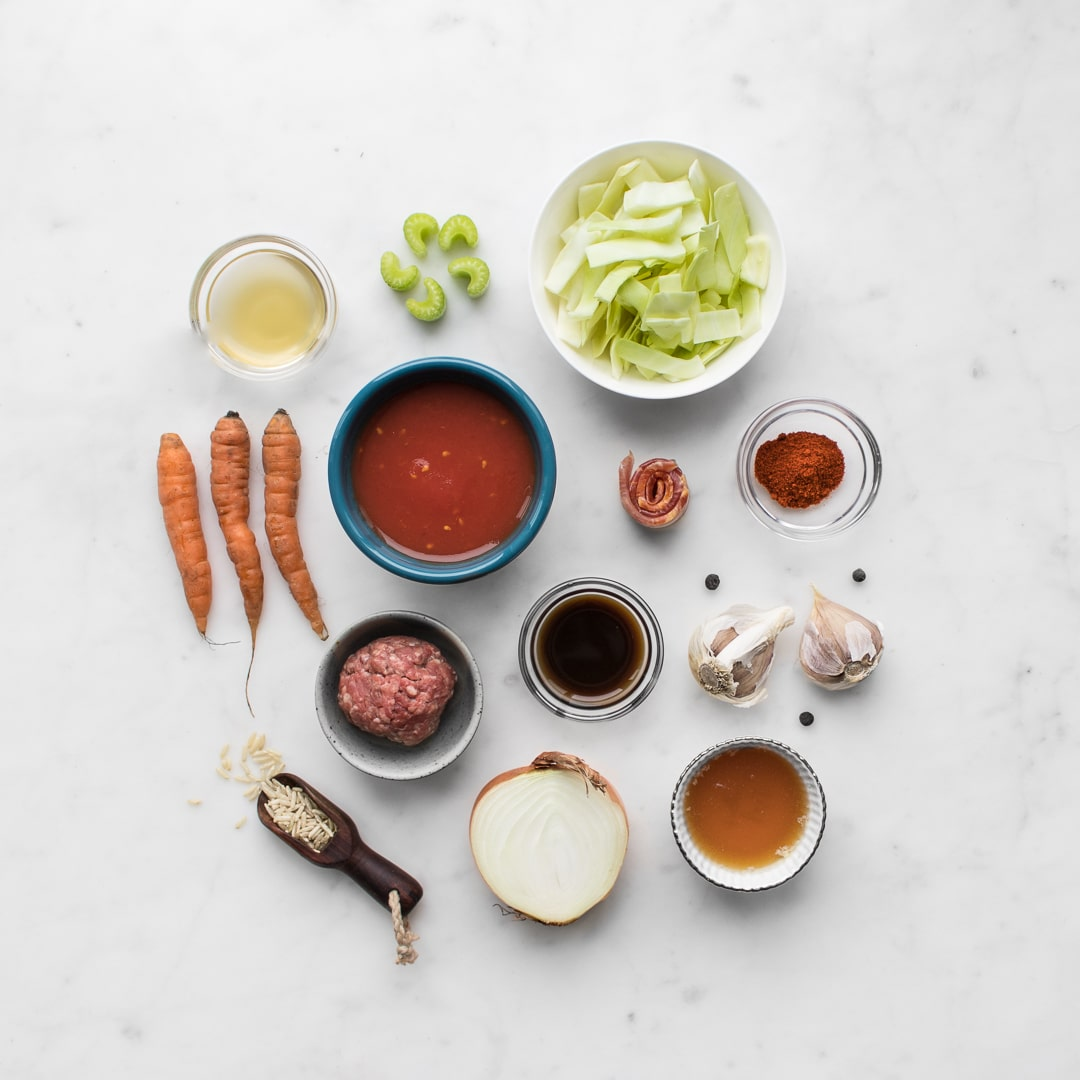 Flat lay photo of ingredients before prep. Cabbage, tomatoes, ground beef, carrots, chicken stock, celery, garlic, onions, rice, bacon.