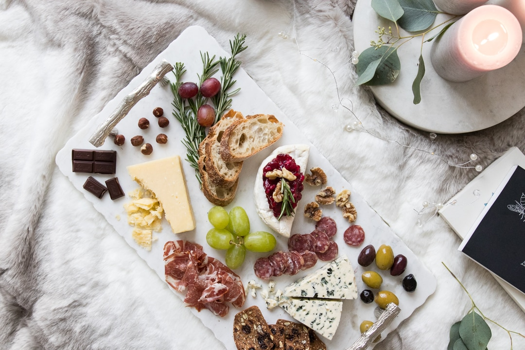 Comforting cheeseboard styled on a marble tray with cheese, meat, chocolate, olives, fruit, and crackers.
