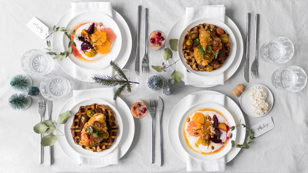 Overhead shot of table setting for holiday brunch with beet and orange salad on yogurt and fried chicken and waffles