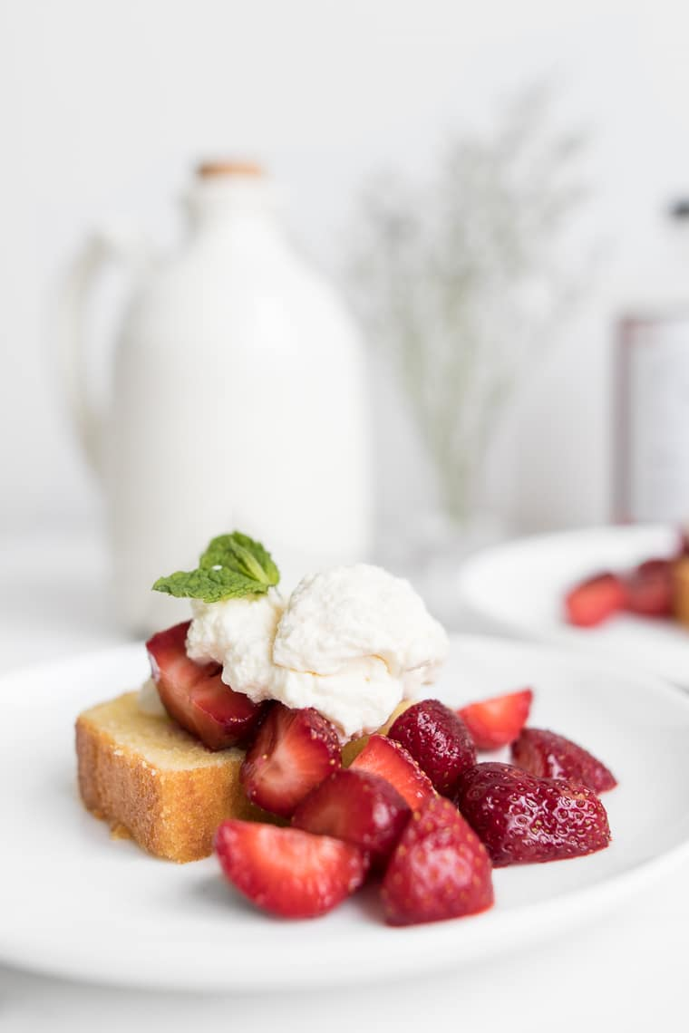 Side view of Strawberry Shortcake Cake with Mascarpone Cream and Strawberries with Maple Syrup Jug in Background