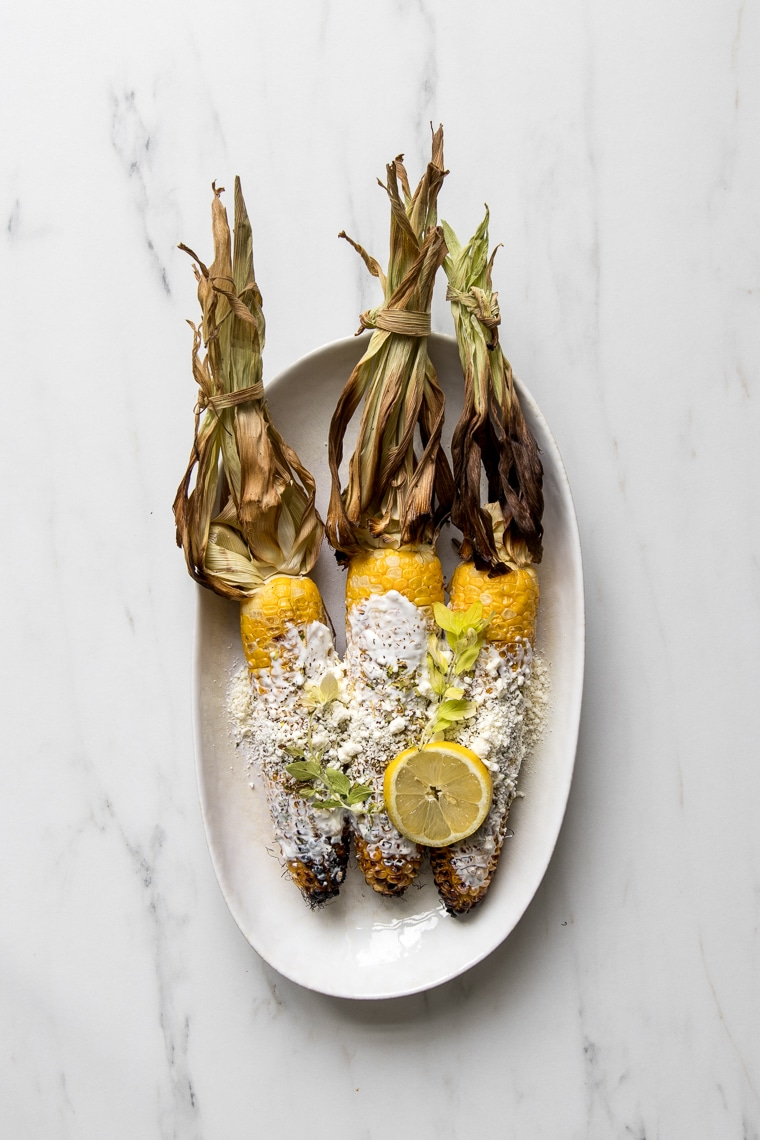 A plate with 3 grilled Greek street corn cobs