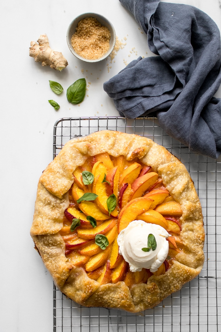 Peach galette cooling on a wire rack with a scoop of ice cream