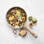 Green shakshuka in a pan with tomatillos and bread
