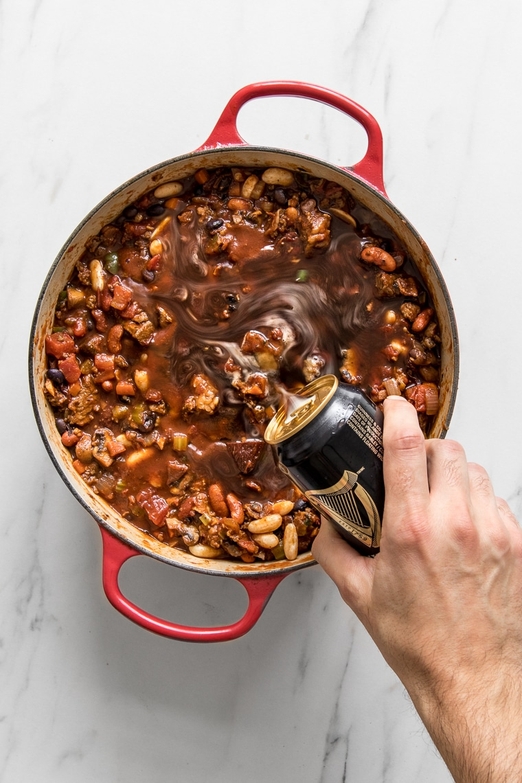 Hand pouring beer into the chili pot from above