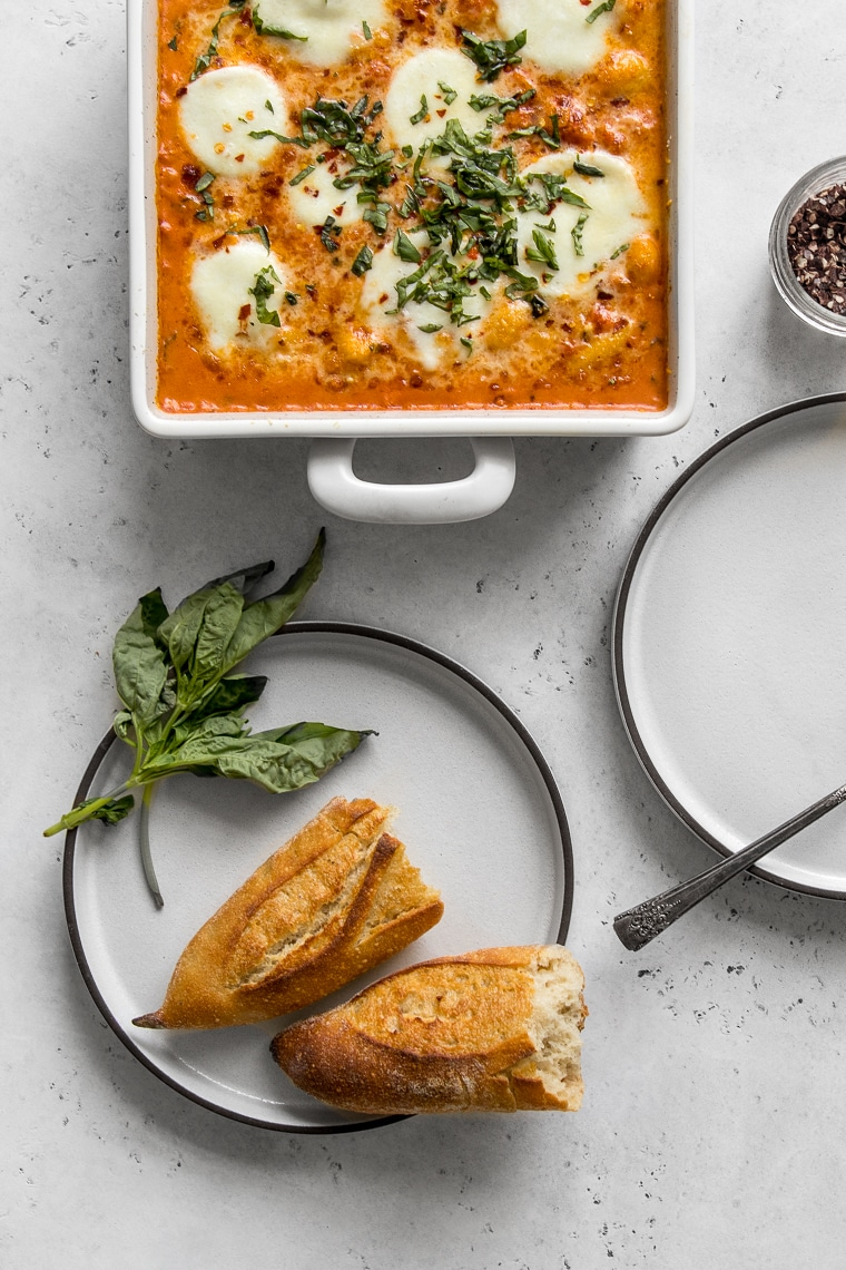 Baking dish with Baked Gnocchi with Vodka sauce and two empty plates