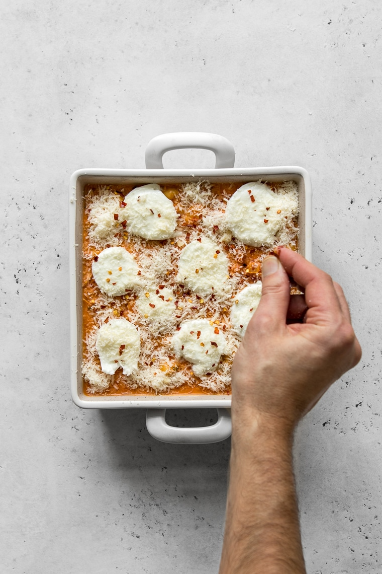A baking dish with Gnocchi alla Vodka being topped with parm and mozzarella