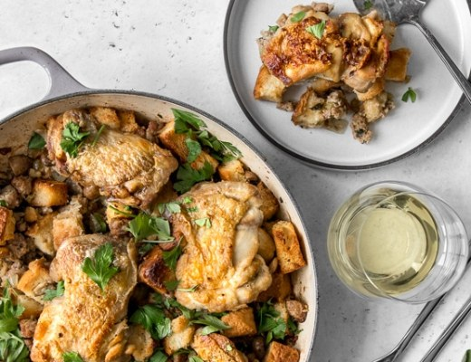 One Pot Chicken and Stuffing in a casserole and plated on a dish, with a glass of white wine