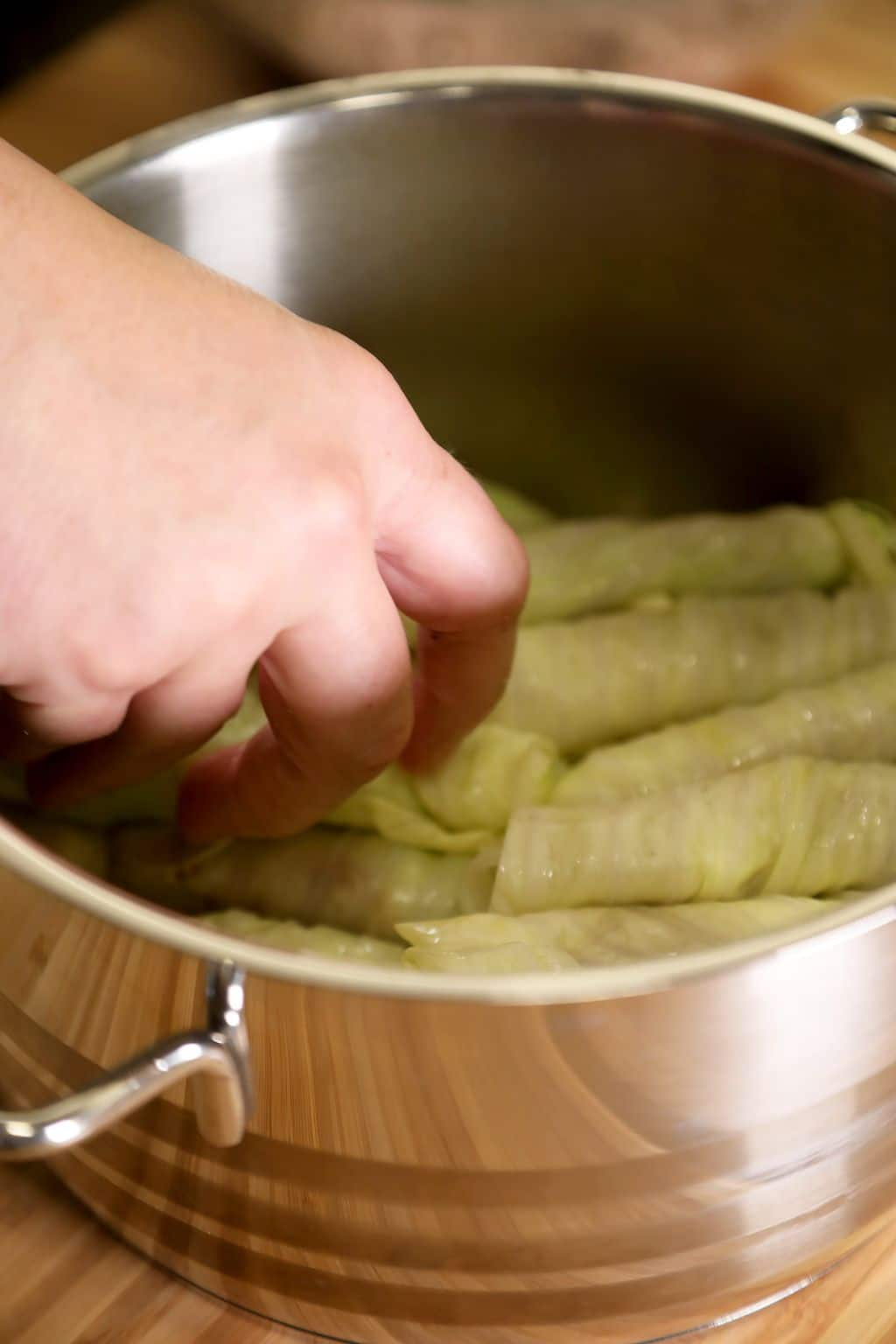 placing rolled cabbage leaves in pot