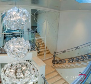 The central staircase in a private Sandhurst residence required Cherryhill to make a bespoke mirror frame stretching over 4 meters tall.