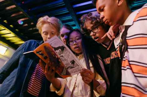 A group of teens appear surprised by a comic book.