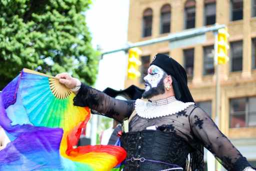 A man wearing an elaborate black dress waves a rainbow fan with streamers attached.