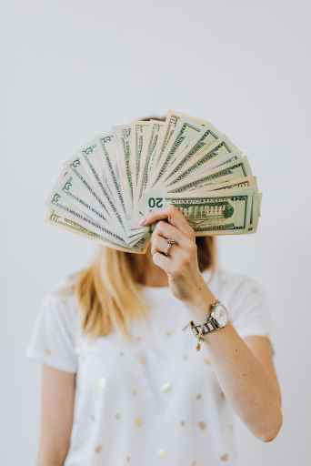 Money, like the dollar bills this woman holds in front of her face, is often used to argue for fewer ownvoices book contracts.