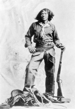 Nat Love, pictured here with a rifle and cowboy gear, went West when slavery ended.