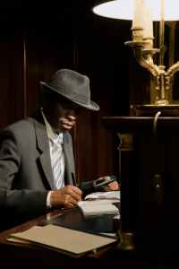 A Black man in a fedora and suit sits at a desk, jotting notes under the light of an old-style lamp. Maybe he's solving a mystery.