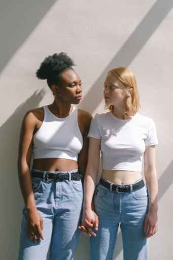A young Black woman and a young white woman wearing matching white t-shirts and high-rise blue jeans hold hands and look at each other longingly.