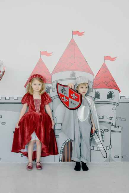 Two children dressed up as a princess (left) and a knight (right) in front of a castle background.