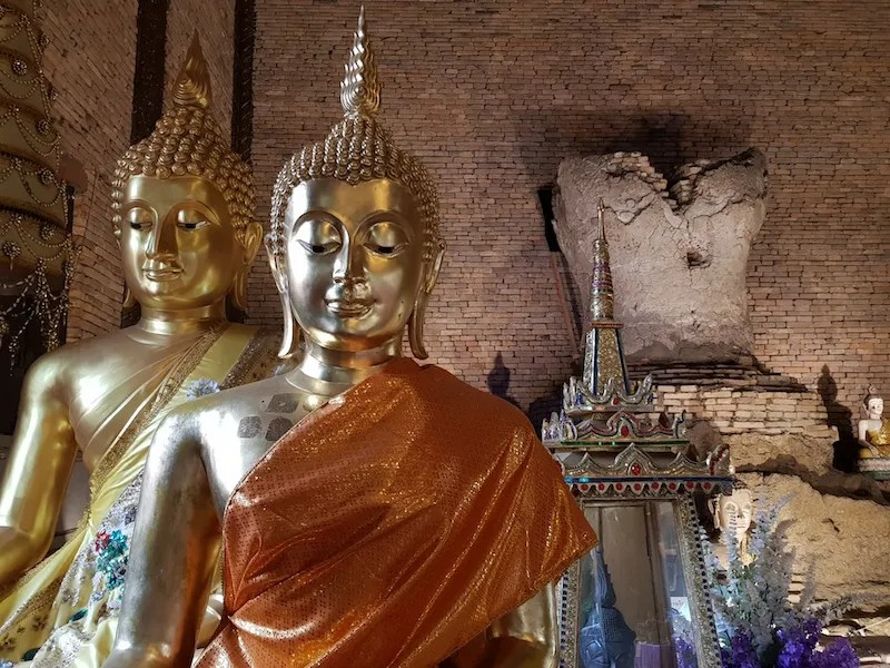 Two Buddha statues in a brick room