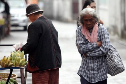 An elderly woman hugs herself against the cold.