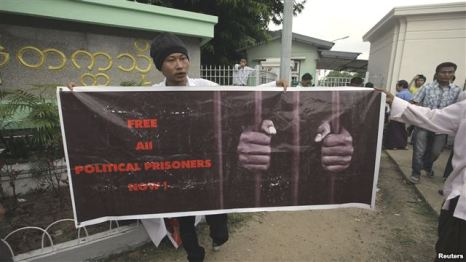 A man holds a poster calling for the freedom of political prisoners in front of the Rangoon University